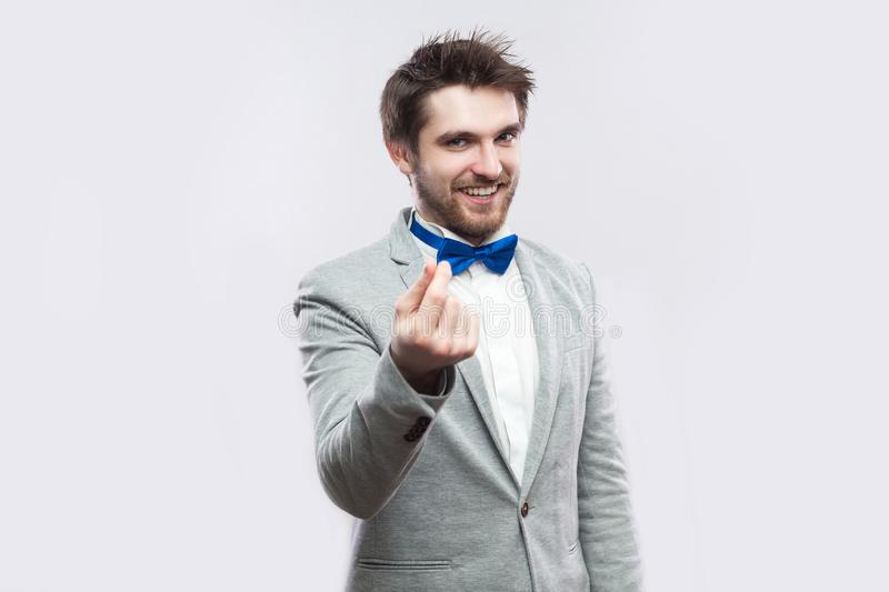 Portrait of funny handsome bearded man in casual grey suit, blue bow tie standing with money gesture hand and looking at camera royalty free stock images
