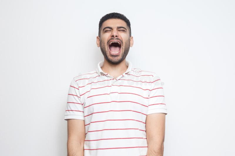 Portrait of funny handsome bearded young man in striped t-shirt standing with closed eyes and laughing royalty free stock photography