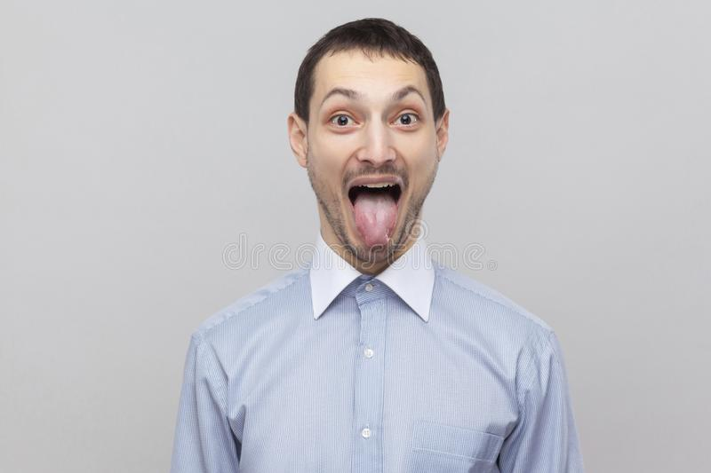 Portrait of funny handsome bristle businessman in classic light blue shirt standing and looking at camera with tongue out and big. Eyes. indoor studio shot royalty free stock photos