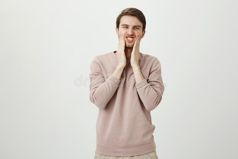 Portrait of funny handsome caucasian male squeezing cheeks with both hands and squinting at camera, standing against. Gray background. Guy looks in mirror and stock images