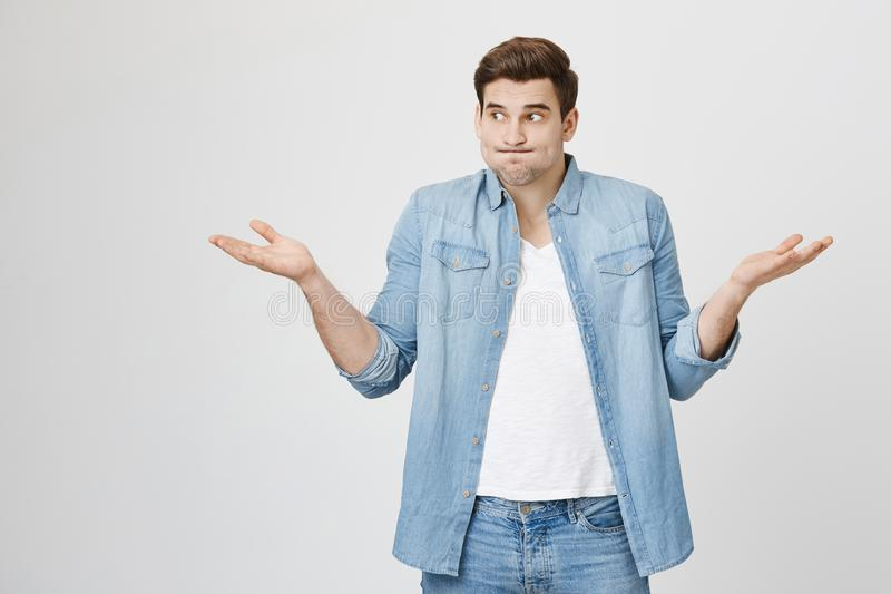 Portrait of funny handsome guy, shrugging and spreading hands, expressing unknowladge and confusion, widen eyes. Standing over gray background. I do not know royalty free stock images