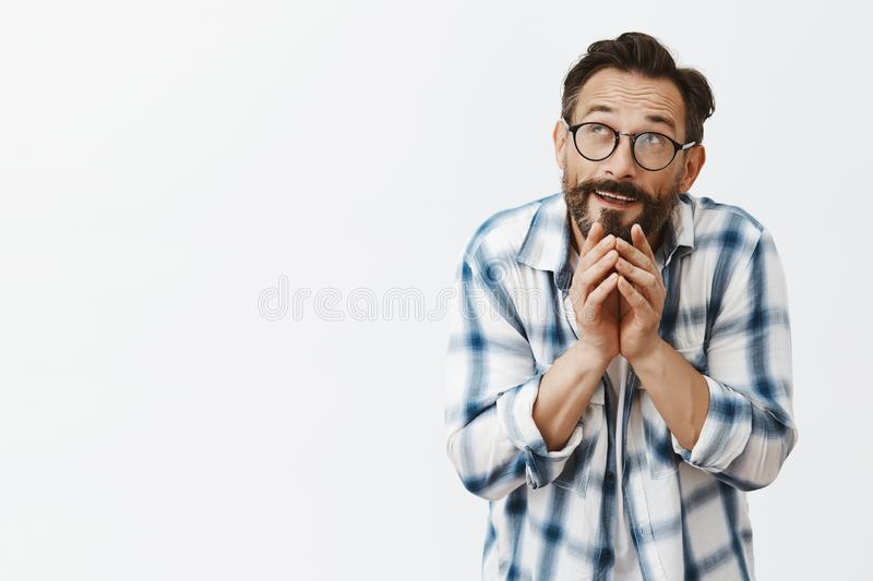 Portrait of funny handsome mature dark-haired man with beard in fancy glasses bending body and steeping fingers saying royalty free stock photos