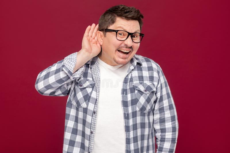 Portrait of funny handsome middle aged business man in casual checkered shirt, eyeglasses standing with hand on ears and looking royalty free stock images