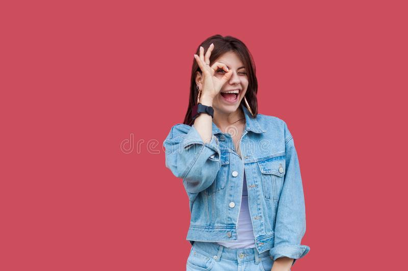 Portrait of funny happy beautiful brunette young woman with makeup in denim casual style standing with Ok sign on her eyes and. Looking at camera. indoor studio stock image