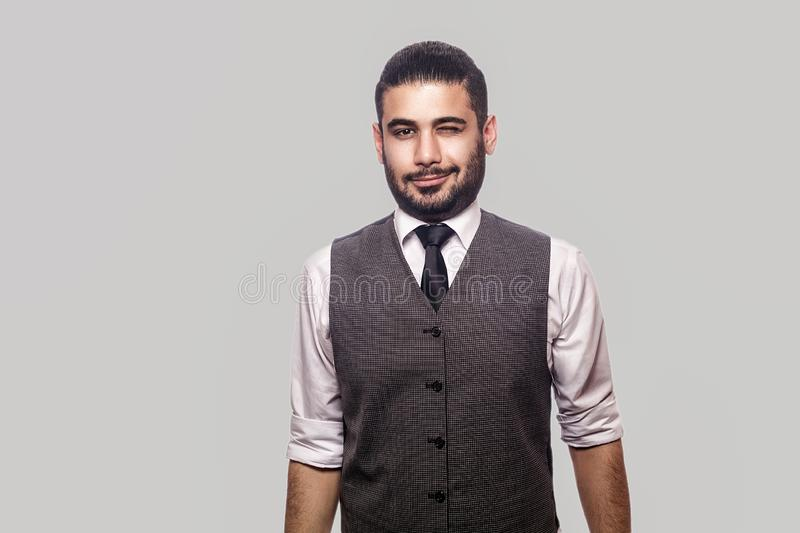 Portrait of funny happy handsome bearded brunette man in white shirt and waistcoat standing, smiling and winking and looking at stock images