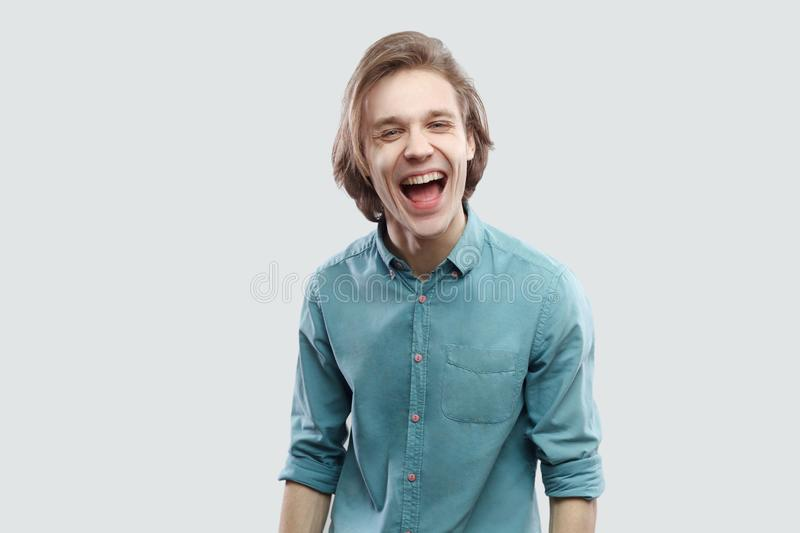 Portrait of funny happy handsome long haired blonde young man in blue casual shirt standing, laughing and looking at camera stock images