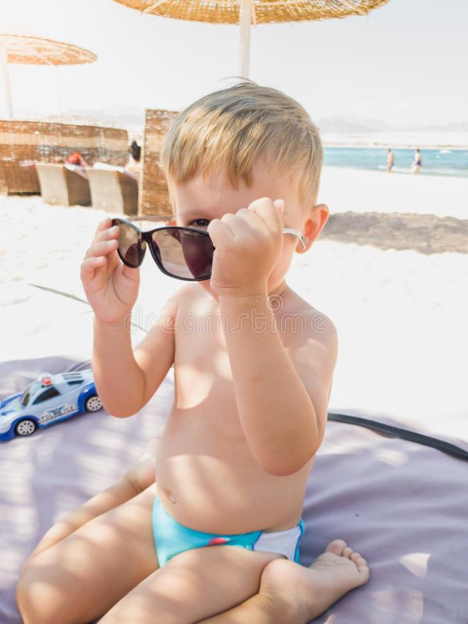 Portrait of funny little boy playing and trying on sunglasses on the sea beach royalty free stock photo
