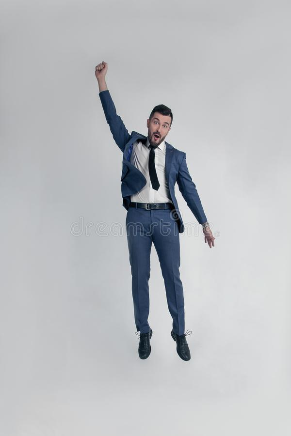 Portrait of a funny and little crazy businessman man jumping and cheering loud isolated on a white background royalty free stock images