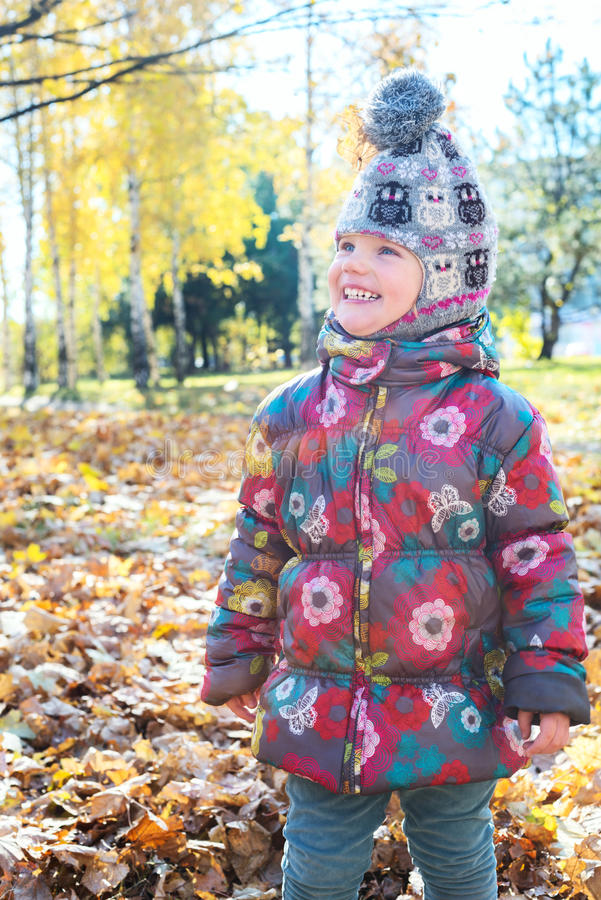 Portrait of funny little girl in autumn park stock photography