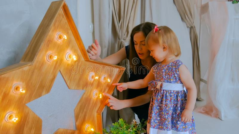 Portrait of funny little girl and her mother at home stock photography