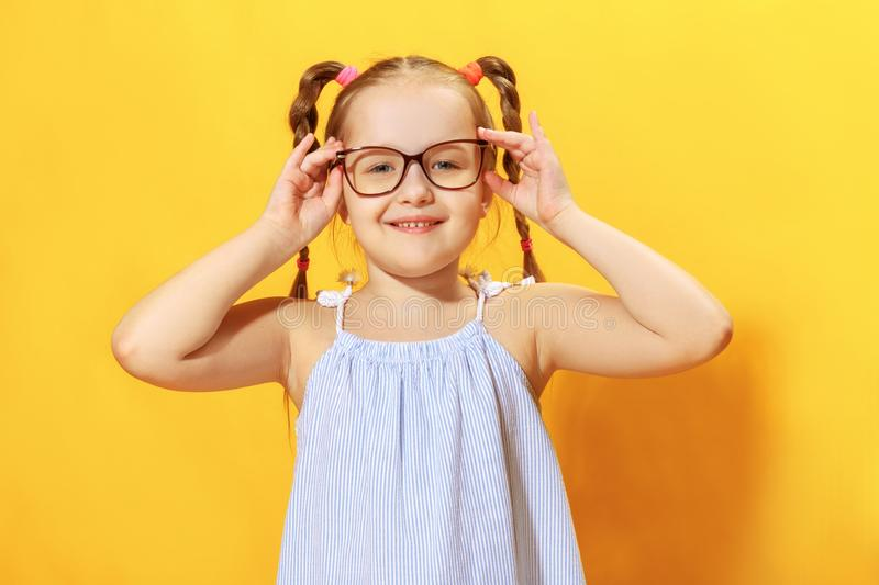 Portrait of a funny little girl on a yellow background. Preschool child straightens glasses.  royalty free stock photos