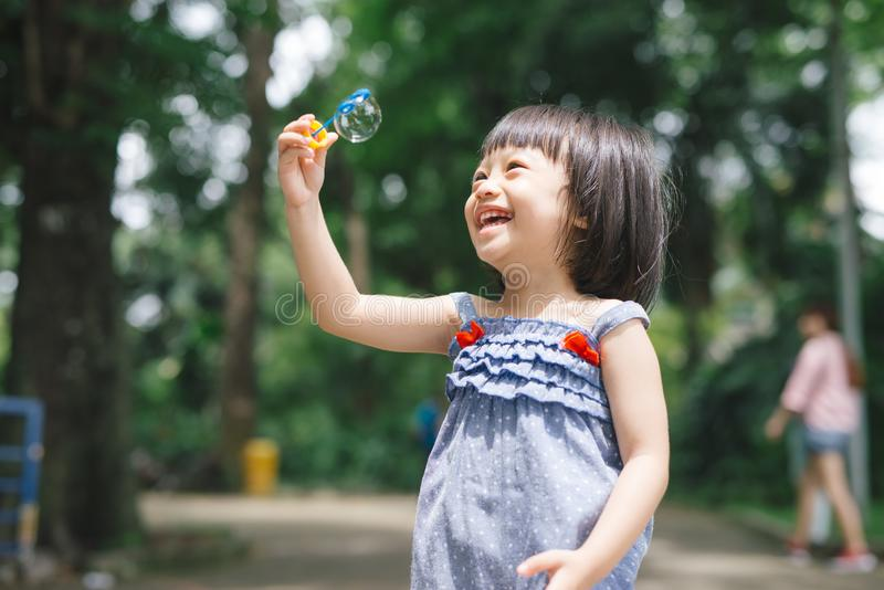 Portrait of funny lovely little girl blowing soap bubbles stock photos