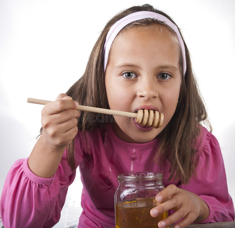 Download Portrait Of Funny Lovely Little Girl Eat Honey Stock Images - Image: 27079684