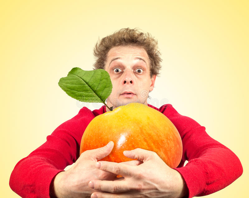 Portrait of funny man with apple stock photos