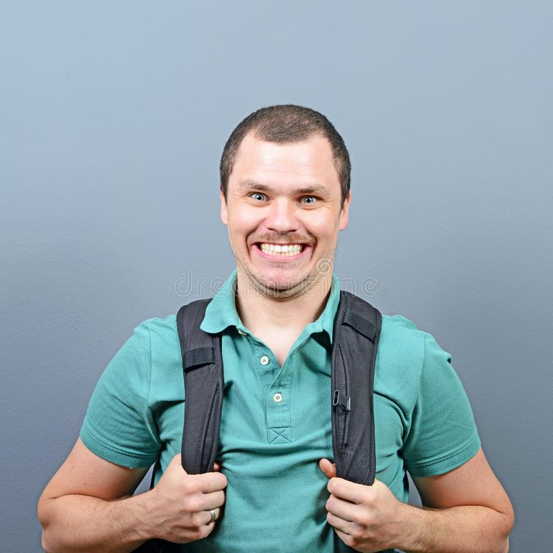 Portrait of a funny man with backpack against gray background royalty free stock images