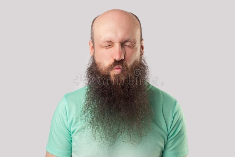 Portrait of funny middle aged bald man with long beard in light green t-shirt standing with closed eyes and kissing lips stock photography