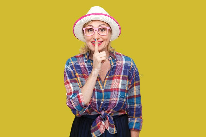 Portrait of funny modern stylish mature woman in casual style with hat and eyeglasses standing looking at camera and asking to. Keep secret between us. indoor stock photography