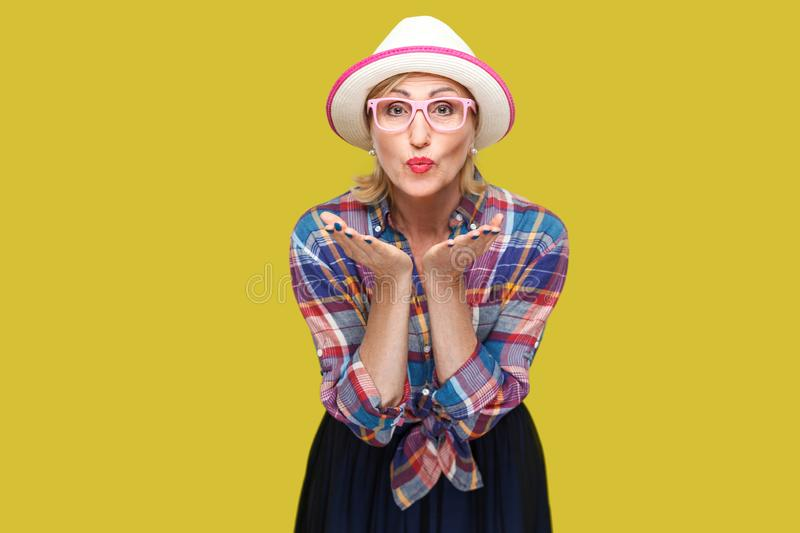 Portrait of funny modern stylish mature woman in casual style with hat and eyeglasses standing sending kiss and looking at camera. With romantic expression royalty free stock photography