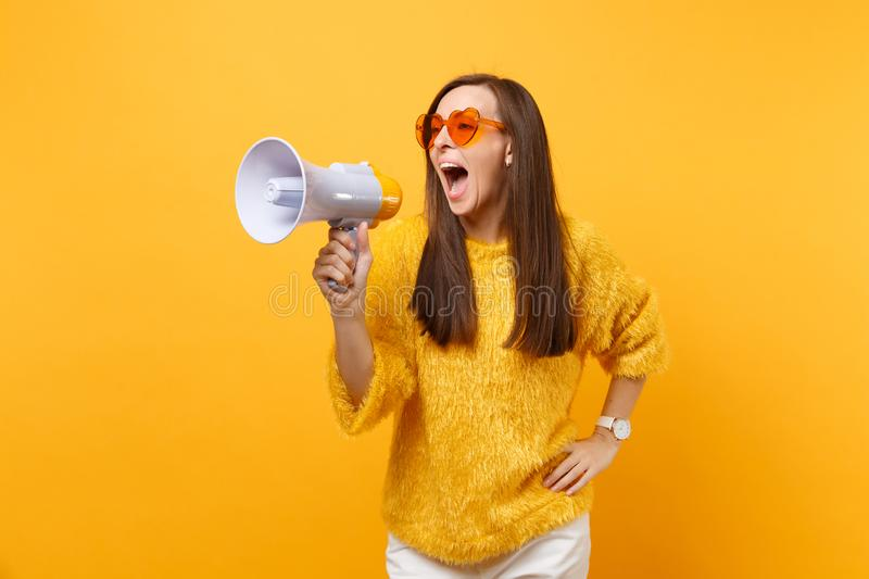 Portrait of funny pretty young woman in fur sweater, orange heart eyeglasses screaming on megaphone isolated on bright. Yellow background. People sincere stock photography