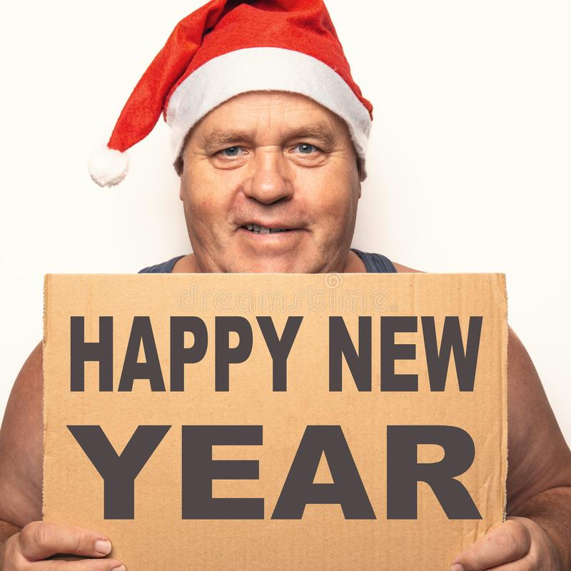 Portrait of funny senior man in red Santa Claus Christmas hat holds cardboard with inscription Happy New Year in hands royalty free stock photography