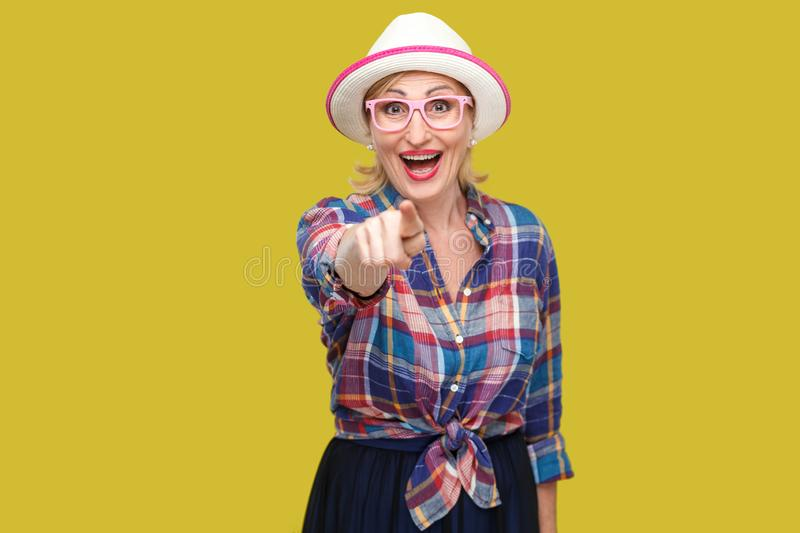 Portrait of funny surprised modern stylish mature woman in casual style with hat and eyeglasses standing, looking and pointing at. Camera with amazed face royalty free stock photos