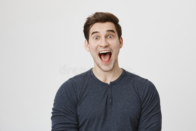 Portrait of funny weird guy shouting with popped-eyes at camera, expressing joy and happiness over gray background royalty free stock images