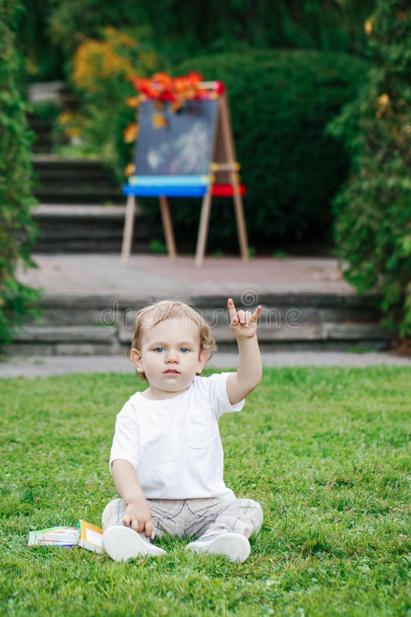 Portrait of funny white Caucasian toddler child kid boy sitting on grass ground outside in summer autumn park by drawing easel royalty free stock photo