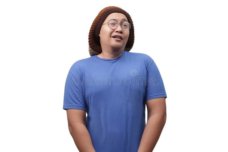 Funny Man Urinating. Portrait of a funny young Asian man in blue shirt gesturing relieved face with closed eyes when urinating pee in standing position stock photography