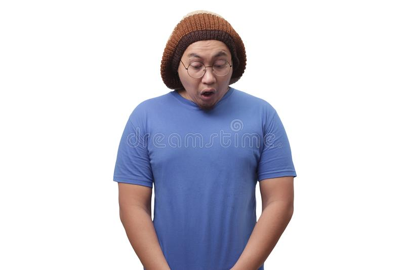 Funny Man Urinating. Portrait of a funny young Asian man in blue shirt gesturing relieved face with closed eyes when urinating pee in standing position stock image