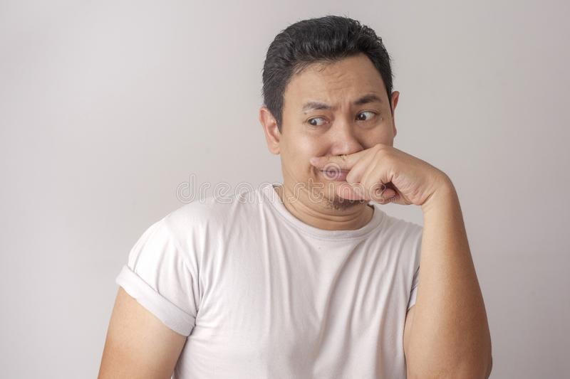 Young Man Close His Nose, Smells Something Bad. Portrait of funny young Asian man closing his nose, smells something bad indonesian malaysian thai japanese royalty free stock photos