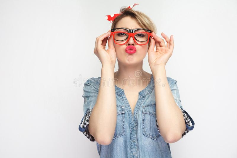 Portrait of funny young girl in casual blue denim shirt with makeup, red headband standing, trying many eyeglasses frames and royalty free stock image