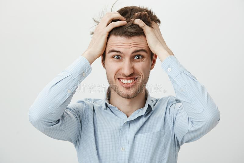 Portrait of funny young man scratching head, grimacing and smiling nervously, meeting deadline and trying to finish work. In time, being bothered with time royalty free stock photo