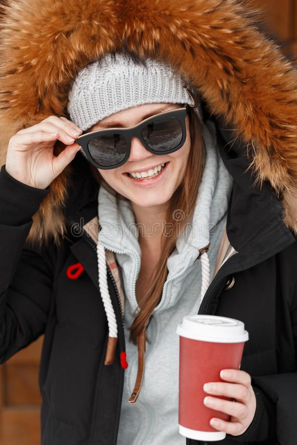 Portrait of a funny young woman hipster with a beautiful smile in sunglasses in a knitted hat in a warm stylish jacket royalty free stock images