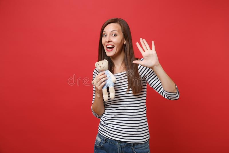 Portrait of funny young woman in striped clothes holding teddy bear plush toy showing palm, waving hand isolated on red. Wall background. People sincere stock photo