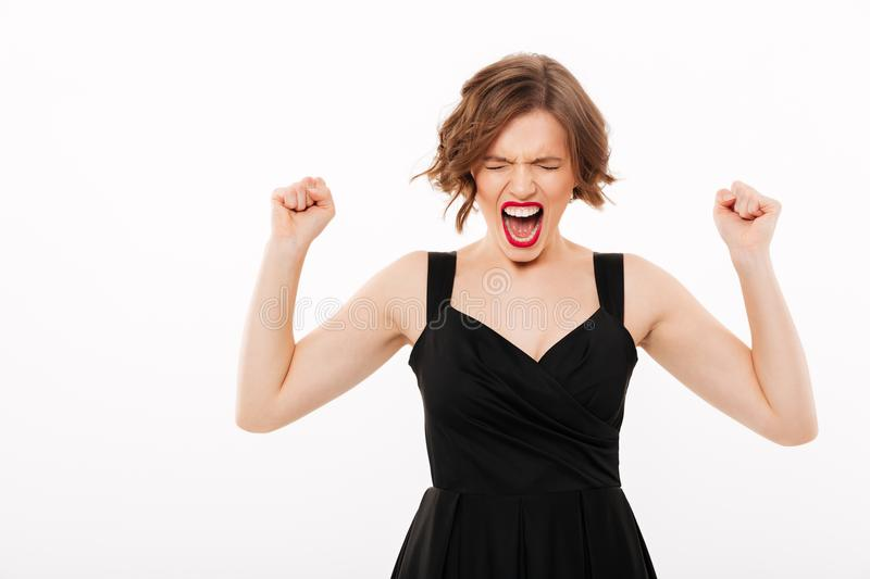 Portrait of a furious girl dressed in black dress screaming. Isolated over white background royalty free stock photos