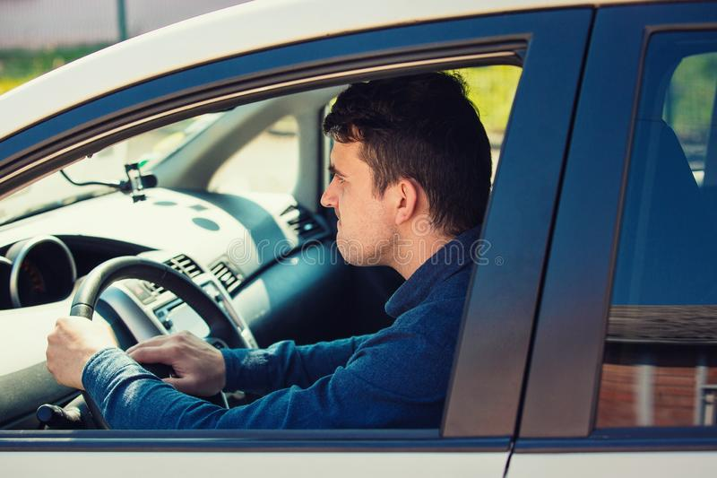 Portrait of furious male driver sitting in the car and honking the car horn angry on the driver ahead. Aggressive guy waiting in the traffic jam, beeping road royalty free stock image