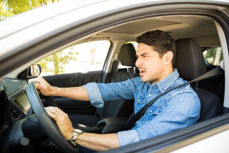 Angry man driving a vehicle. Portrait of furious male driver sitting in the car and honking the car horn stock photos