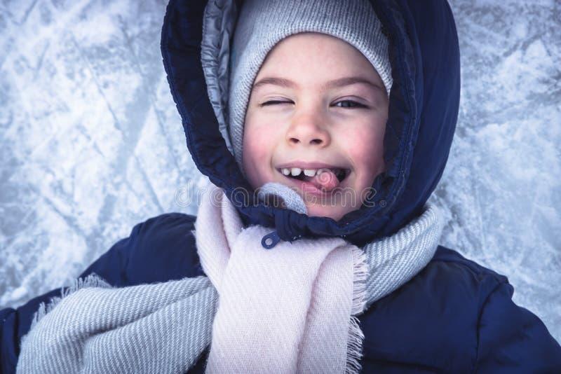 Portrait gai d'enfant d'hiver sur le fond de glace de neige ayant l'amusement sur l'anneau de patinage neigeux pendant des vacanc images libres de droits
