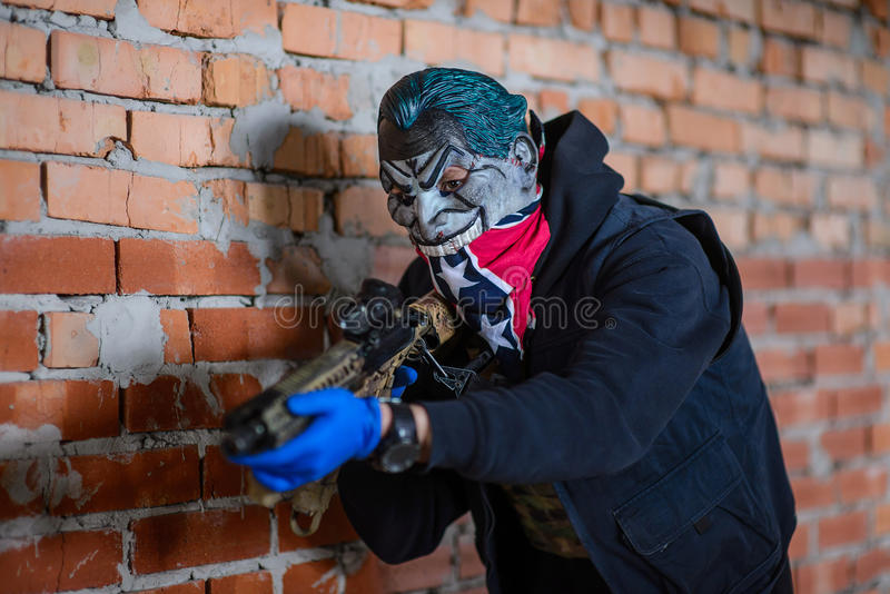 Portrait of gangster in mask with gun. Bandit in mask, bandana, blue gloves with gun on brick wall background.Selective focus stock photography