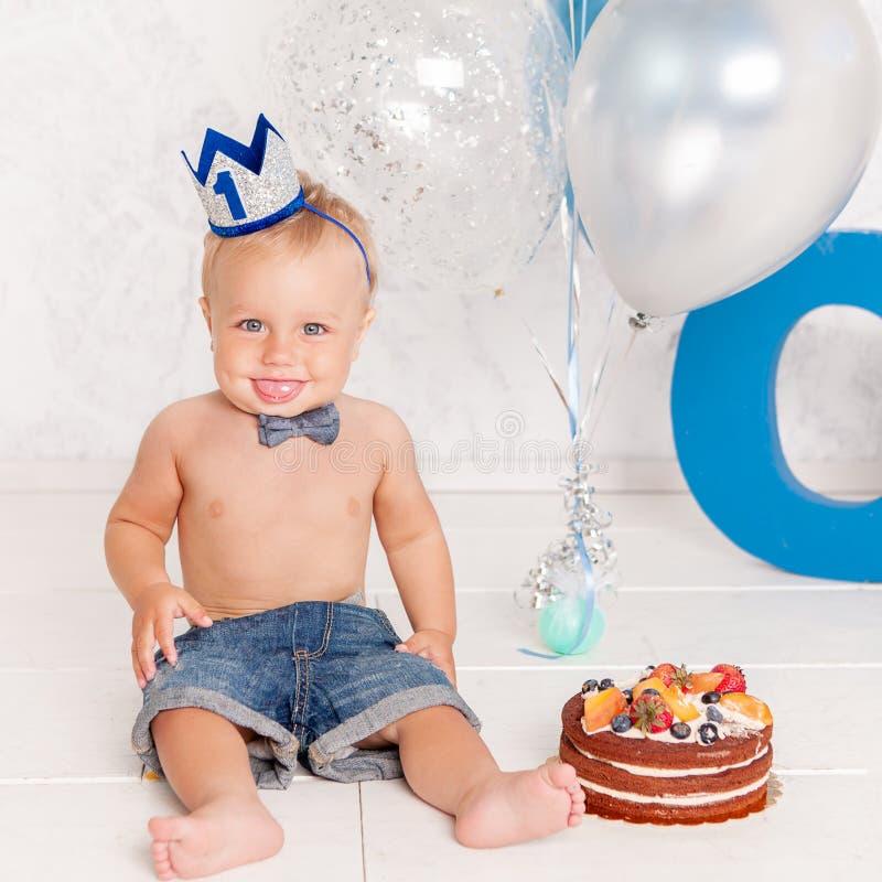 Portrait garçon drôle de mode de petit dans le studio avec de grands lettres, ballons et gâteau bleus images libres de droits