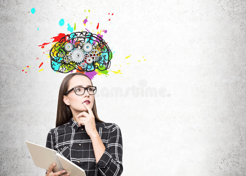 Portrait of a geek girl in glasses and brain cogs. Portrait of a geek girl in glasses standing near a concrete wall with a copybook and a colorful brain with stock photos