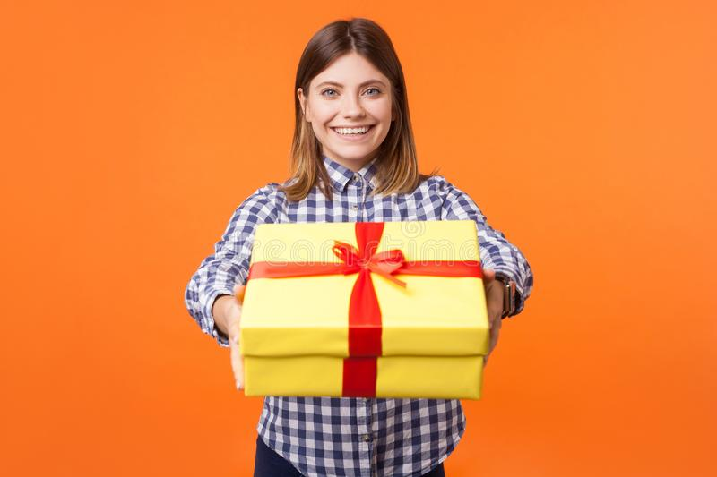 Portrait of generous friendly young woman with brown hair in casual checkered shirt. indoor studio shot isolated on orange. Portrait of generous friendly young royalty free stock images