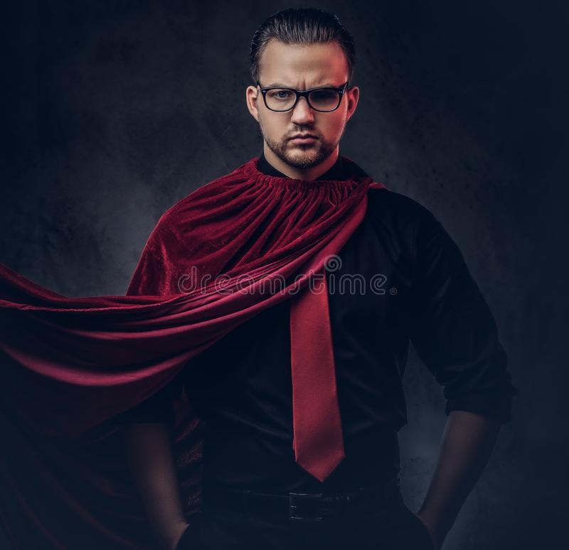 Portrait of a genius villain superhero in a black shirt with a red tie. royalty free stock photo
