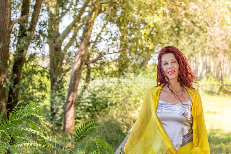 German mature woman in a green garden. Portrait of German mature woman with yellow shawl and silver top smiling in a green garden stock photo