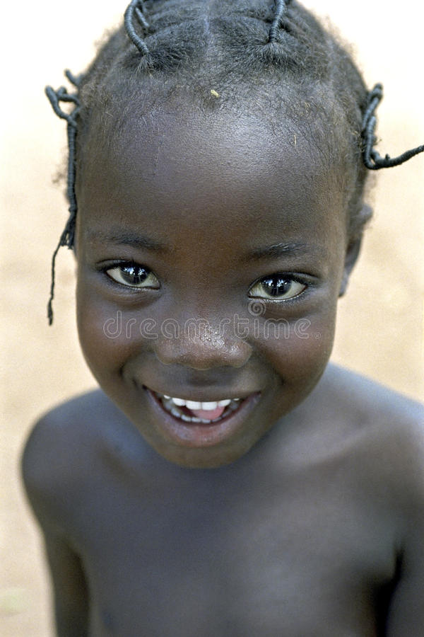 Portrait of Ghanaian young girl with radiant face. Ghana, city Bolgatanga [northern Ghana]: closeup of a Ghanaian girl. The child is shy and watch with happy stock images