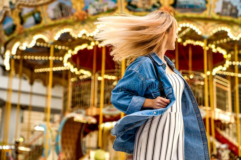 Portrait of a girl in American style on a swing laughs and rejoices.  royalty free stock photo