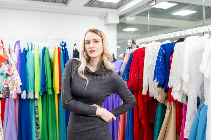 Portrait of a girl on the background of clothes on hangers in the clothing store. Happy young woman choosing clothes stock photos