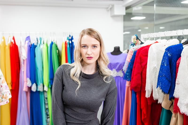 Portrait of a girl on the background of clothes on hangers in the clothing store. Happy young woman choosing clothes royalty free stock photography