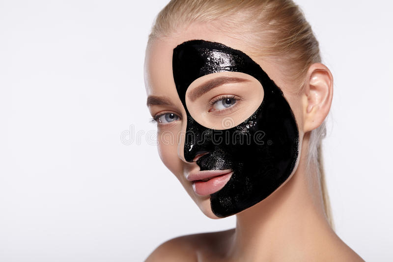 Portrait of girl with black cosmetic mask on her face. Close-up portrait of attractive girl with black cosmetic mask on her face royalty free stock photo