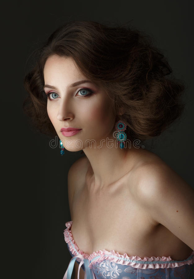Portrait of a girl with blue eyes. A woman wearing a corset. stock photo